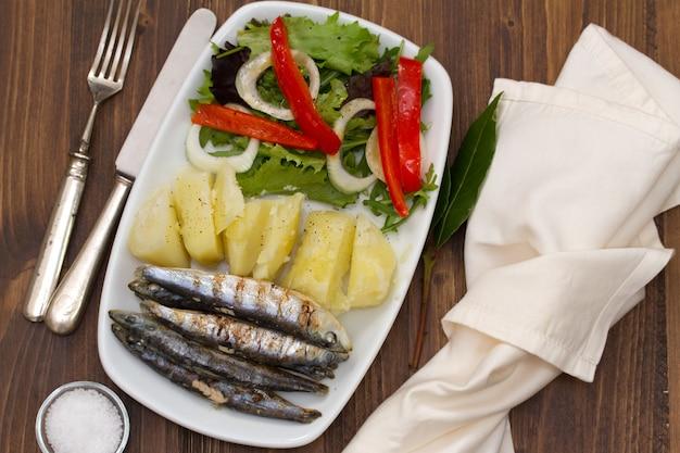 茶色の木製の白い皿にポテトとサラダと揚げイワシ Premium写真