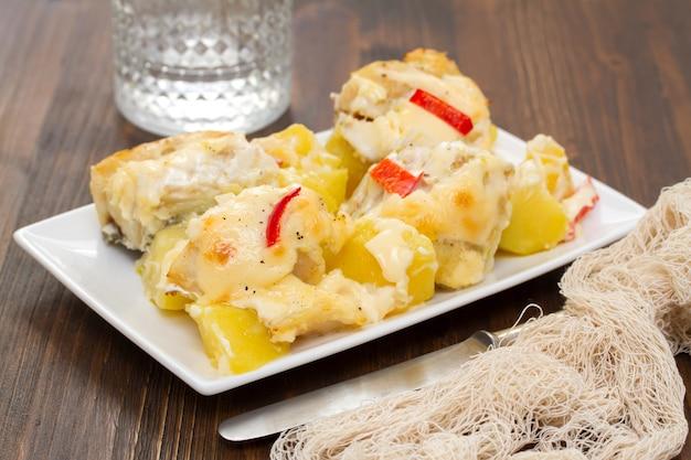 ジャガイモと白い皿にソース添えタラ魚 Premium写真