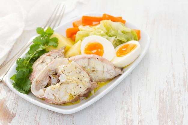白い皿に野菜をゆでた魚 Premium写真