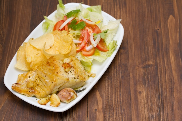 ポテトとサラダの皿に揚げたタラ Premium写真