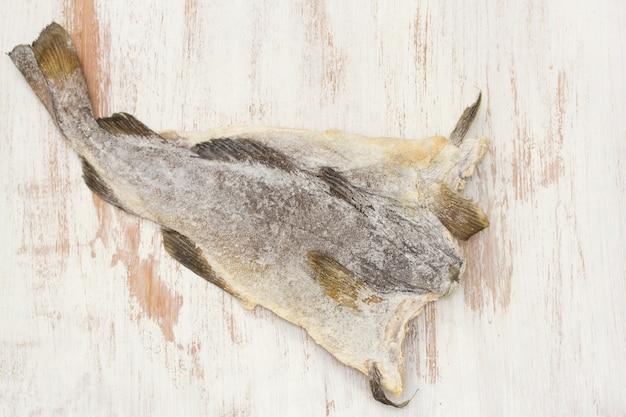 Рыба сухая соленая треска на деревянной поверхности Premium Фотографии