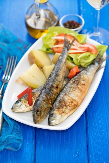 Жареные сардины с отварным картофелем и салатом на белой тарелке Premium Фотографии