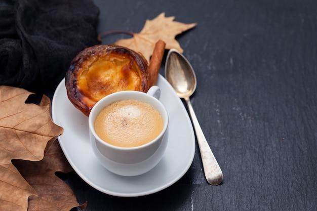 典型的なポルトガルの卵のタルトとコーヒーのカップ Premium写真