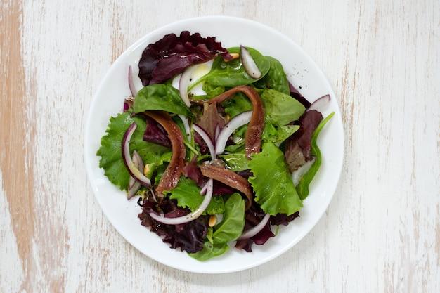 アンチョビと玉ねぎの白い表面に白いプレートのサラダ Premium写真