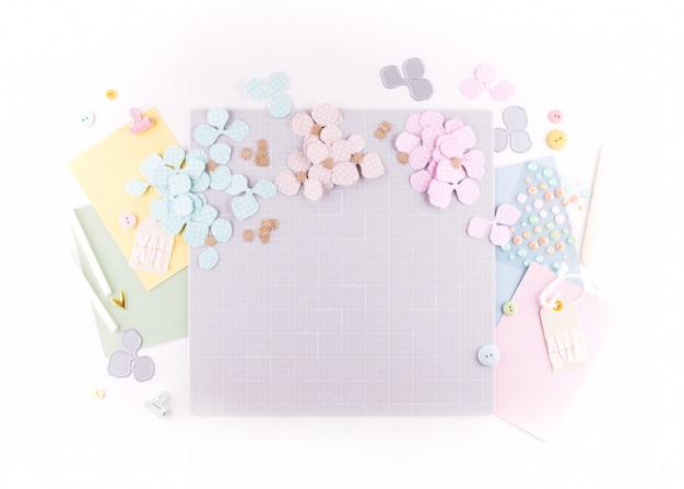 フラット横たわっていた、トップビュークラフトテーブルデスク。カット、はさみ、厚紙、紙、白い背景の上の鉛筆のマットとワークスペース。フローラルリースの装飾を作成します。 Premium写真
