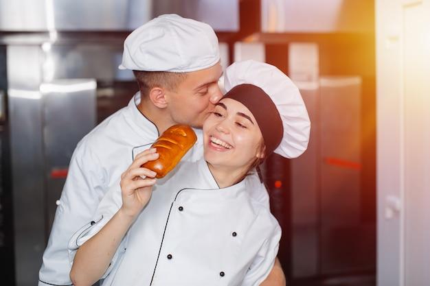 少年ベイカーは、オーブンを背景にパン屋の頬に女の子をキスします。 Premium写真