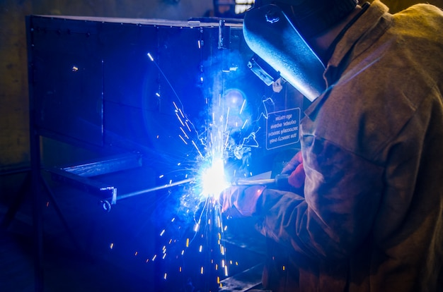 Рабочий в спецодежде и защитной маске сваривает металл сварочным аппаратом Premium Фотографии