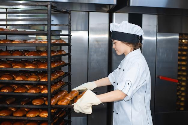 Портрет молодой женщины пекарь с промышленной печи с выпечкой в пекарне Premium Фотографии