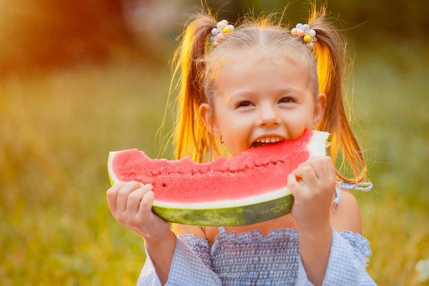 小さな女の子がスイカのスライスをかむ Premium写真