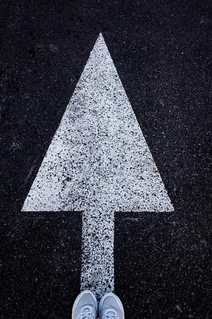 白いスニーカーのアスファルトと足の上に白い矢印。 Premium写真