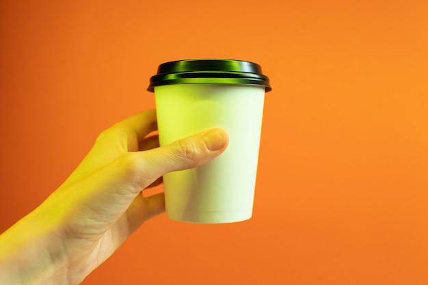 トレンディなネオンの光の手で紙のコーヒーカップ。 Premium写真