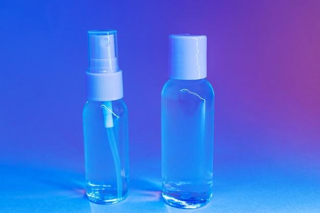 Косметические флаконы с прозрачным лосьоном в модном ярком неоновом свете. Premium Фотографии