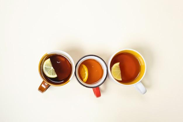 ベージュ色の背景にレモンとお茶のカップ。 Premium写真