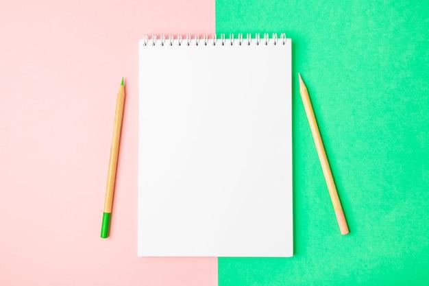 Белая открытая тетрадь на зеленых и розовых предпосылках. рядом находятся карандаши. Premium Фотографии