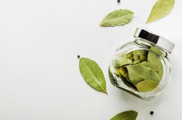 白い背景の上の乾燥月桂樹の葉。スパイス用のガラス瓶。 Premium写真