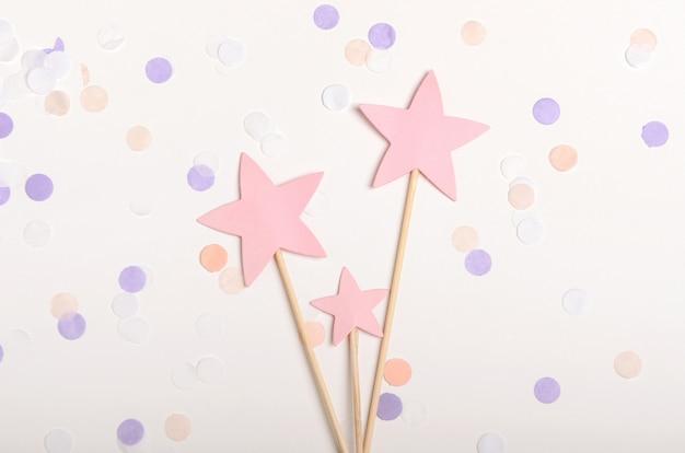 Розовые звезды на палочке сверху на белом фоне с конфетти Premium Фотографии