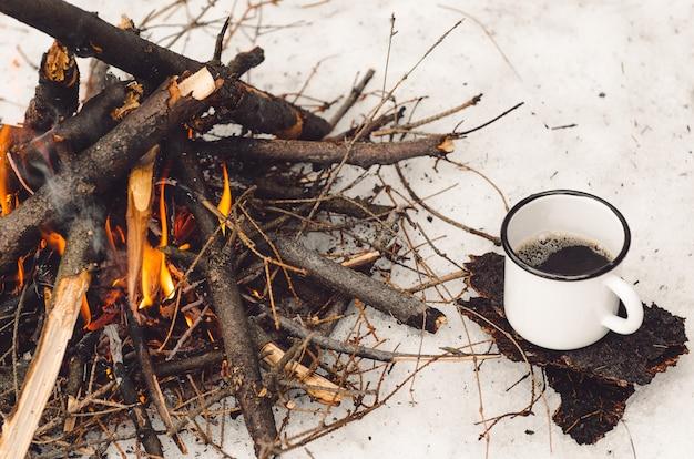 Гуляющая кружка с кофе возле костра. концепт поход, прогулка, поездка зимой Premium Фотографии