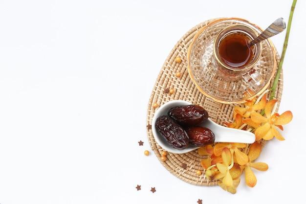 ラマダンの概念と、お茶セットと蘭の花と卵巣のボウルにいくつかの日付 Premium写真
