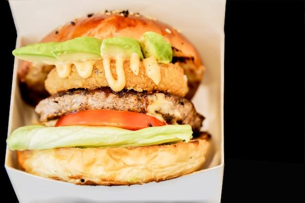 Вид сбоку бургер, показывая его слои в белой коробке и черном фоне Premium Фотографии
