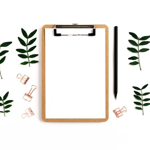 クリップボードはモックアップします。ペーパークリップ、鉛筆、白い背景の上のピスタチオの枝 Premium写真