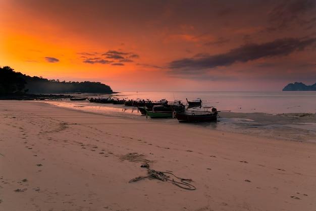 ピピ島にはロングボートがあります。島の上のピンクの夕日。 Premium写真