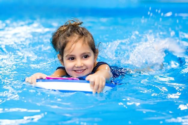 プールで泳ぐことを学ぶ少女 Premium写真