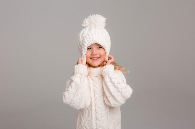 ニットの白い冬の帽子で少し縮れ毛の少女の肖像画 Premium写真