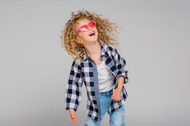 Девочка блондинка девочка в розовых очках улыбается Premium Фотографии