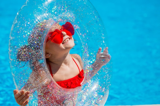 プールで水泳サークルを持つ少女 Premium写真