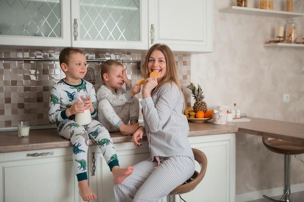 キッチンで朝食を食べている子供を持つ母 Premium写真