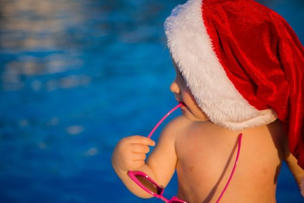 サンタの帽子の赤ちゃんとプールでサングラス Premium写真