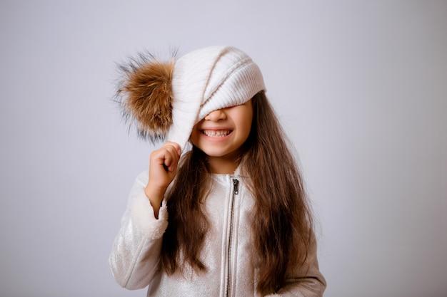白の笑みを浮かべて冬の帽子の少女 Premium写真