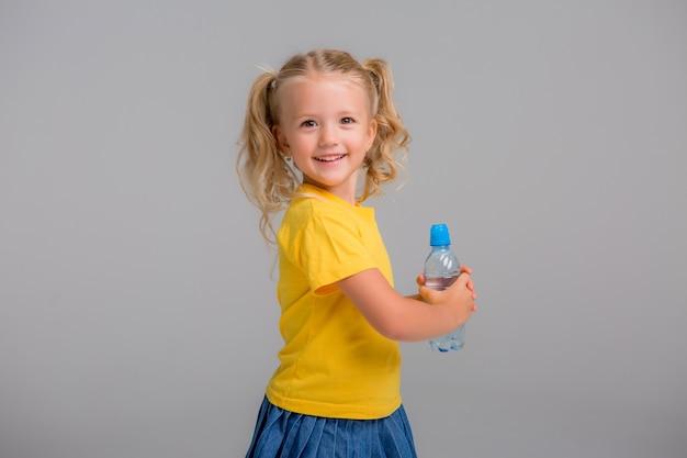水の保持ボトルを笑顔の少女 Premium写真