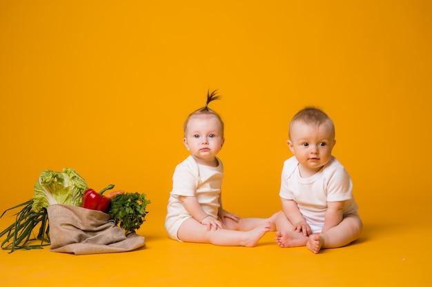 Два мальчика и девочка в окружении свежих овощей в эко сумке на оранжевом Premium Фотографии