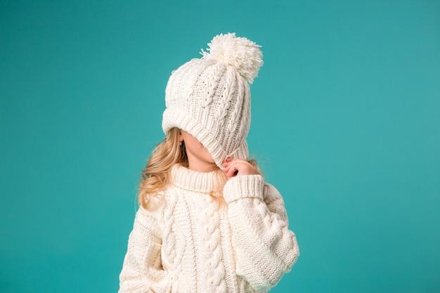 Маленькая девочка зимой вязаная шапка и свитер Premium Фотографии