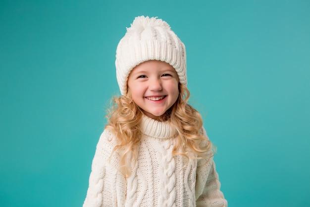 冬の白い帽子とセーターに笑みを浮かべて、スケートを保持している少女 Premium写真