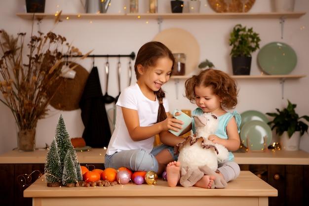 Две девочки едят мандарины в рождественской кухне Premium Фотографии