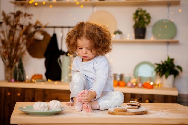 台所でパジャマの女の赤ちゃん Premium写真