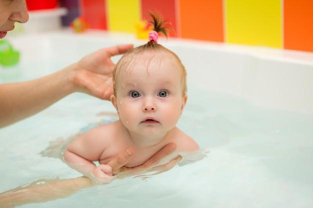Ребенок учиться плаванию, детское плавание, здоровая семья мама обучает ребенка плаванию Premium Фотографии