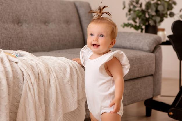 灰色のソファの隣の部屋で健康な女の赤ちゃんが歩くことを学んでいます。 Premium写真