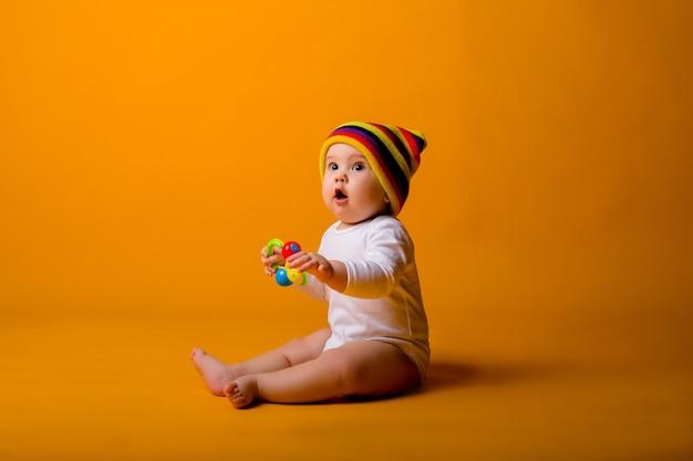 オレンジ色の壁の上に座って、白いボディースーツとおもちゃを保持している色とりどりの帽子の男の子 Premium写真