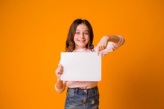 黄色の背景に空白のシートを持って笑っている女の赤ちゃん Premium写真
