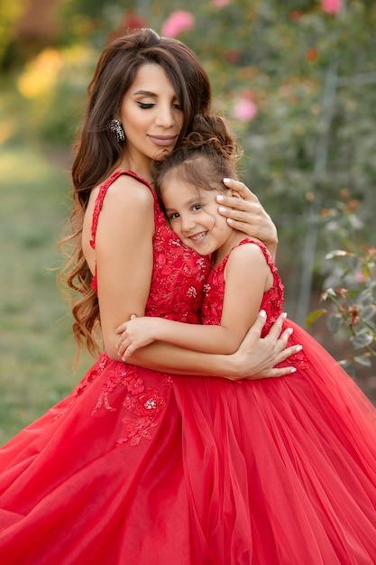 夏のバラ園を歩く赤いイブニングドレスの母と娘 Premium写真