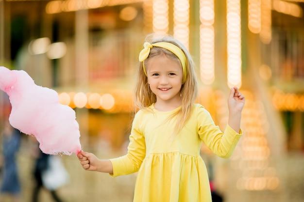 公園を歩いていると綿菓子を食べる女の赤ちゃん Premium写真