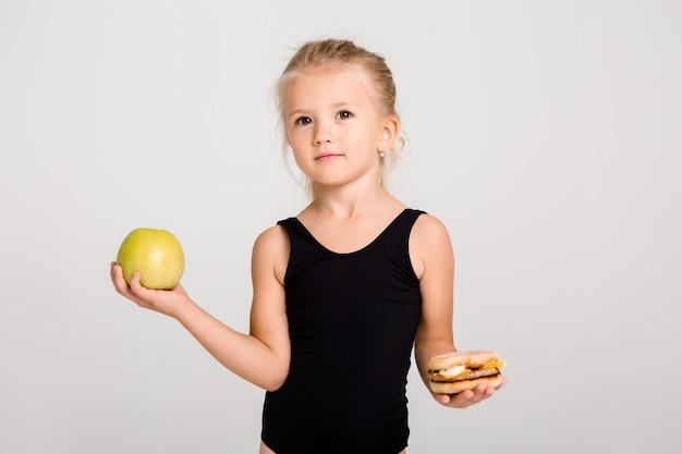 笑っている子供の女の子は、リンゴとハンバーガーを保持しています。健康食品を選ぶ、ファーストフードはない Premium写真