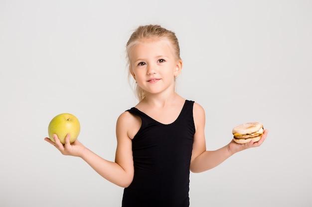 笑っている子供の女の子は、リンゴとハンバーガーを保持しています。健康食品を選ぶ、ファーストフードなし、テキスト用のスペース Premium写真
