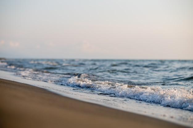 Песчаный пляж и морские волны на закате. грузия, магнети Premium Фотографии