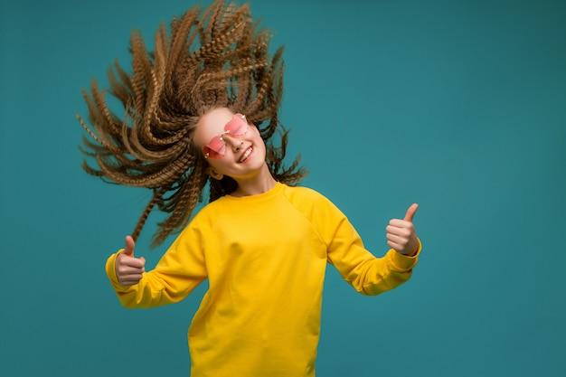 Предподростковый девушка в желтой одежде, улыбаясь Premium Фотографии