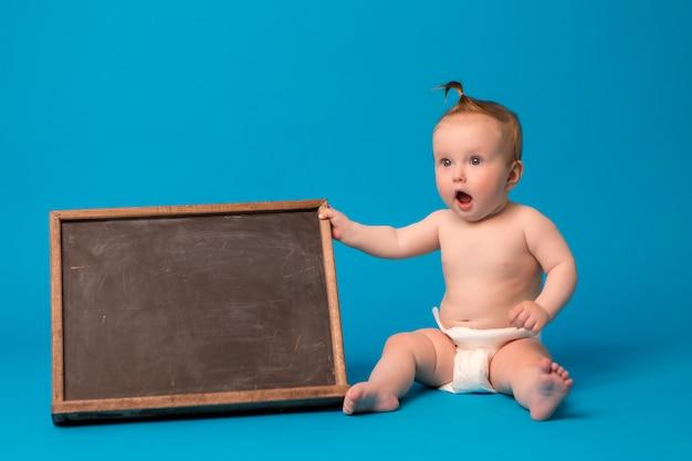 青色の背景に描画ボードを保持しているおむつの女の赤ちゃん Premium写真
