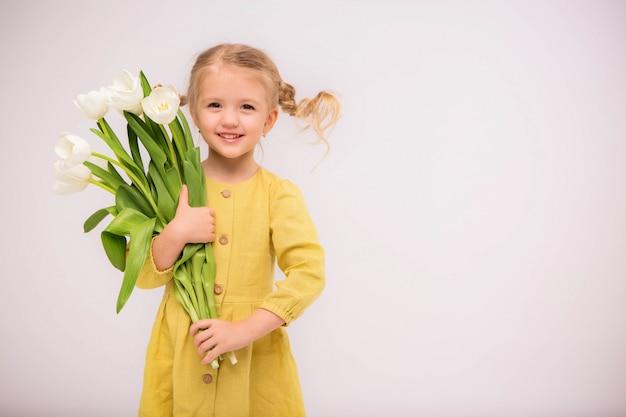 明るい背景にチューリップの花束と赤ちゃん女の子ブロンド Premium写真